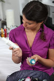 Frau, die Haarpflegemittel betrachtet Lizenzfreies Stockbild