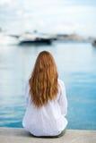 Frau, die am Hafen sitzt stockfoto