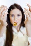 Frau, die Halskette mit gelbem Saphir hält Stockbild