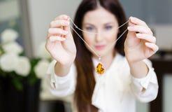 Frau, die Halskette mit gelbem Saphir hält Lizenzfreie Stockfotografie