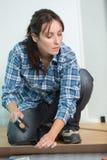 Frau, die Hammer auf Holzfußboden verwendet Lizenzfreies Stockfoto