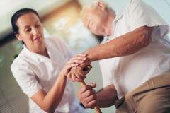 Frau, die Hand des alten Mannes mit Spazierstock hält stockbilder