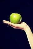 Frau, die an Hand einen Apfel hält Stockfotografie