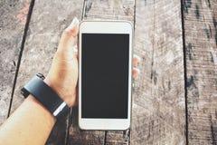 Frau, die an Hand intelligentes Telefon und aufpassen verwendet stockfotografie