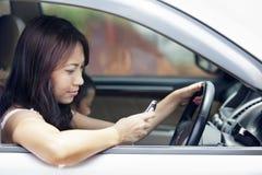 Frau, die Handy beim Antreiben verwendet Lizenzfreie Stockfotos