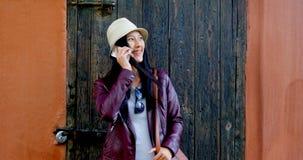 Frau, die am Handy beim Lehnen auf Wand 4k spricht stock video