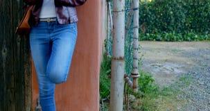 Frau, die Handy beim Lehnen auf Wand 4k verwendet stock footage