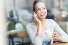 Frau, die Handy am Café verwendet Stockfotografie