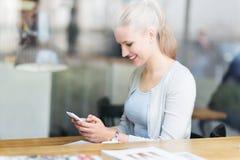 Frau, die Handy am Café verwendet Stockfotos
