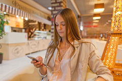 Frau, die Handy am Café verwendet Lizenzfreie Stockfotografie