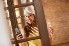 Frau, die am Handy durch Fenster schaut Lizenzfreies Stockfoto