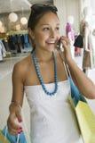 Frau, die Handy im Bekleidungsgeschäft verwendet Stockbild