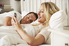 Frau, die Handy im Bett verwendet, während Ehemann schläft lizenzfreie stockfotografie
