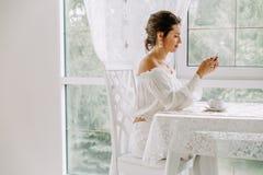 Frau, die Handy im Café verwendet Weibliche Hand mit Smartphone und Kaffee Lizenzfreies Stockbild