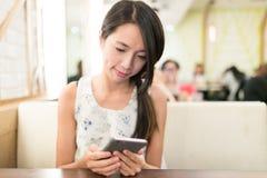 Frau, die Handy im Restaurant verwendet Lizenzfreie Stockbilder
