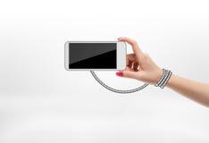 Frau, die Handy mit dem gezogenen Seil eingewickelt um ihre Hand auf weißem Hintergrund hält Stockbilder
