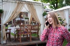 Frau, die am Handy nahe Straßenrestaurant spricht Stockfoto