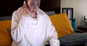 Frau, die am Handy spricht und Laptop auf Bett verwendet stock video
