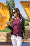 Frau, die Handy am städtischen Park verwendet Lizenzfreie Stockbilder