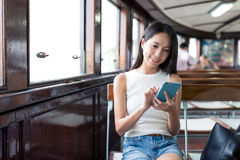 Frau, die Handy verwendet und Fähre in Hong Kong nimmt lizenzfreie stockfotos