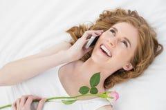Frau, die Handy verwendet, während das Stillstehen im Bett mit stieg Stockfoto