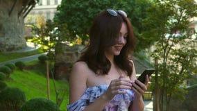 Frau, die am Handy, Zeitlupe, Kamerastabilisatorschuß geht und spricht stock video footage