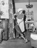 Frau, die Hausarbeit mit einem Staubsauger tut (alle dargestellten Personen sind nicht längeres lebendes und kein Zustand existie stockbild