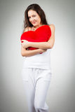 Frau, die heart-shaped Kissen anhält Stockfoto