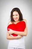 Frau, die heart-shaped Kissen anhält Lizenzfreie Stockbilder