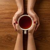 Frau, die heiße Tasse Tee mit Plätzchen auf Holztisch hält Lizenzfreie Stockfotos