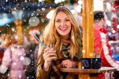 Frau, die heißen Durchschlag auf deutschem Weihnachtsmarkt trinkt Lizenzfreie Stockfotografie
