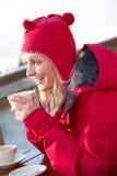 Frau, die heißes Getränk im Kaffee am Skiort genießt Lizenzfreies Stockfoto