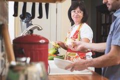 Frau, die am Helfer beim Arbeiten in der Küche lächelt Stockfoto