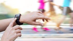 Frau, die herauf Herzfrequenz vom smartwatch auf dem Leutelaufen überprüft Lizenzfreies Stockfoto