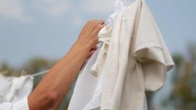 Frau, die herauf nasse Wäscherei auf Wäscheleine hängt stock video