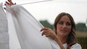 Frau, die herauf nasse Wäscherei auf Wäscheleine hängt stock video footage