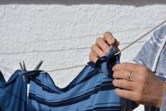 Frau, die herauf die Wäscherei mit hölzernen Kleiderhaken hängt stockfotografie