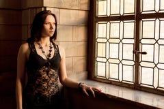 Frau, die heraus beflecktes Fenster anstarrt Stockbilder