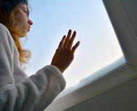 Frau, die heraus das Fenster schaut stockfotos