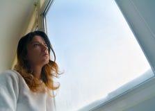 Frau, die heraus das Fenster schaut stockfoto