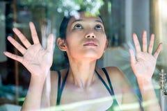 Frau, die heraus durch Fenster schaut Lizenzfreies Stockbild