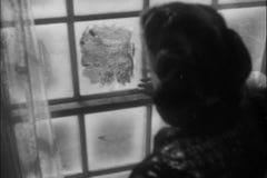 Frau, die heraus eisiges Fenster schaut stock footage