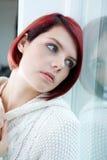 Frau, die heraus Fenster mit traurigem Ausdruck schaut Lizenzfreie Stockbilder