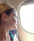 Frau, die heraus Flugzeugfenster schaut Lizenzfreie Stockfotos