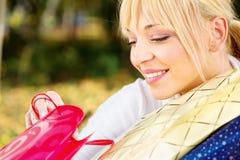 Frau, die heraus Tascheninhalt überprüft Stockbild