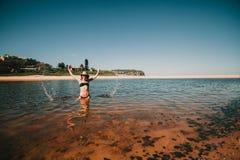 Frau, die heraus Wasser mit den Händen am Strand in Australien spritzt Lizenzfreies Stockfoto