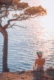 Frau, die heraus zum Meer schaut Stockbilder