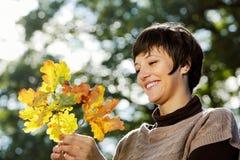 Frau, die Herbstblätter betrachtet Lizenzfreie Stockfotos