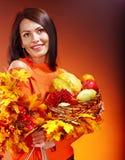 Frau, die Herbstkorb hält. Lizenzfreies Stockfoto