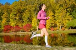 Frau, die in Herbstpark, schönes Mädchenläuferrütteln läuft Stockbild